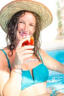 Femme brune de beauté de mode dans la piscine buvant le cocktail
