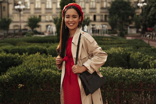 Femme brune en béret rouge et robe lumineuse sourit à l'extérieur