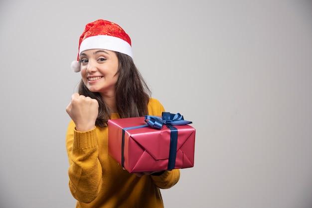 Femme brune en bonnet de noel montrant son poing et tenant la boîte-cadeau.