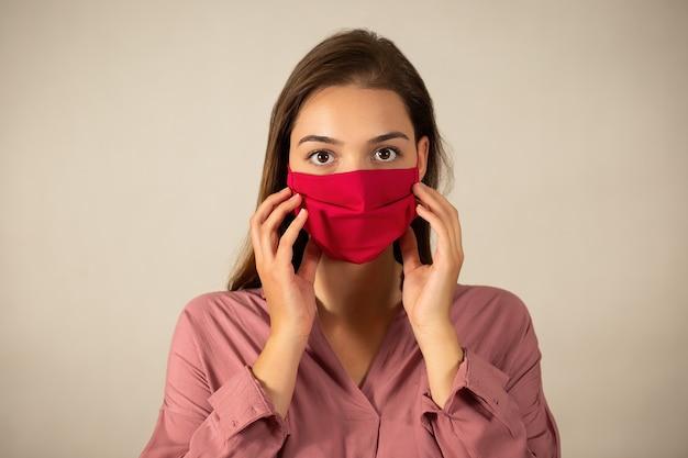 Femme brune avec la bouche couverte à la recherche de l'appareil photo