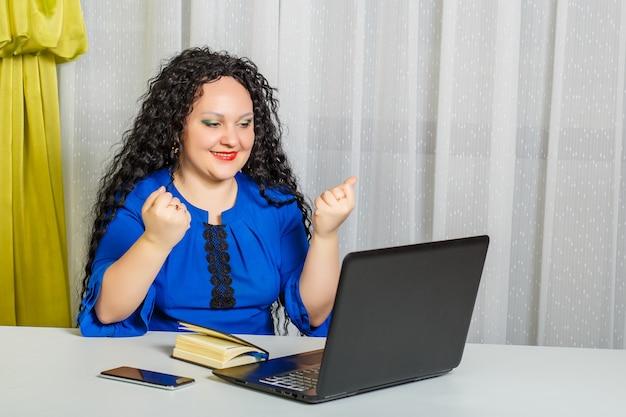 Femme brune bouclée est assise à une table dans le bureau communique émotionnellement via la communication vidéo. photo horizontale
