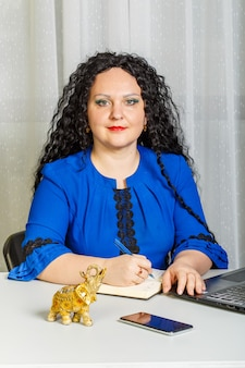 Femme brune bouclée est assise à la table dans le bureau avec un ordinateur portable