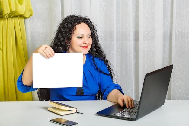Une femme brune bouclée est assise à une table dans le bureau, tient une feuille dans le papier et tape sur l'ordinateur. photo horizontale