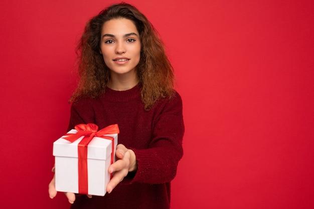 Femme brune bouclée isolée sur mur de fond rouge portant un pull rouge tenant une boîte-cadeau regardant la caméra.