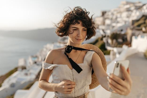 Une femme brune bouclée en robe beige et chapeau de paille prend un selfie sur la mer et le mur de la ville