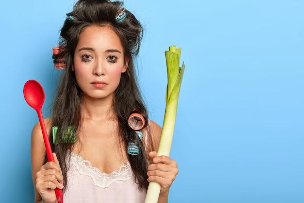 Une femme brune bouleversée pleure car elle a beaucoup de travail à la maison, ne peut pas préparer quelque chose de délicieux, a gâté le maquillage, tient le poireau vert et la cuillère n'a pas d'humeur pour la cuisine