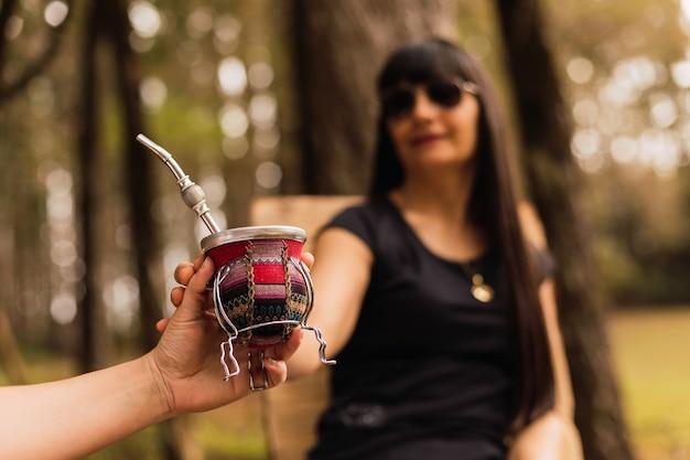 Femme brune buvant du thé maté. femme avec des lunettes de soleil, boire une infusion de compagnon. focus à portée de main.