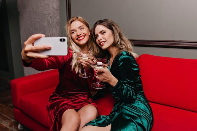 Femme brune buvant du vin pendant que son amie fait selfie. portrait intérieur de filles détendues assis sur un canapé rouge.