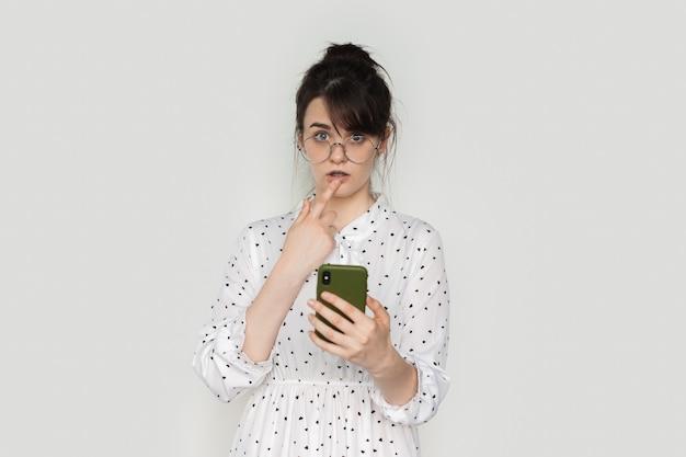Une femme brune caucasienne étonnée touche ses lèvres tout en tenant un téléphone sur un mur blanc