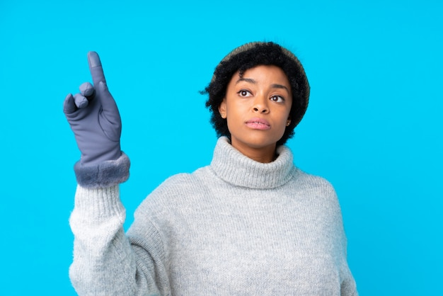 Femme brune avec un chapeau d'hiver sur fond bleu isolé