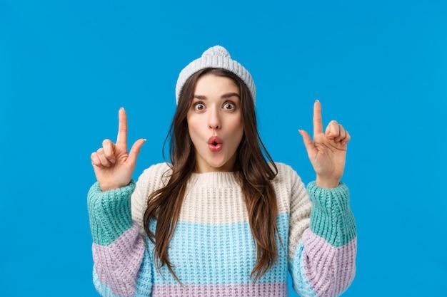 Femme brune avec chapeau d'hiver et pull pointant vers quelque chose