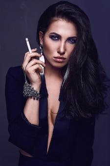 Femme brune chaude élégante fumant une cigarette