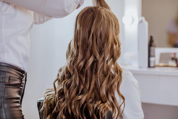 Femme brune en chemise blanche faisant la coiffure bouclée pour jolie fille adolescente aux cheveux longs.