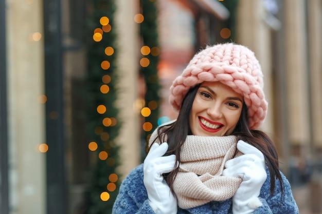 Femme brune chic en manteau marchant dans la ville en hiver. espace libre
