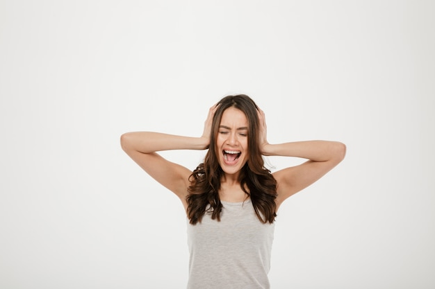 Femme brune en colère criant et couvrant ses oreilles sur gris