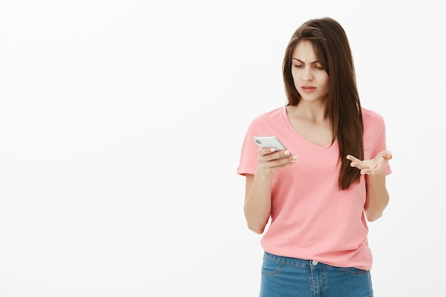 Femme brune confuse posant dans le studio avec son téléphone