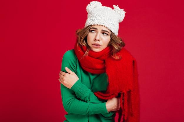Femme brune confuse en pull, chapeau drôle et écharpe