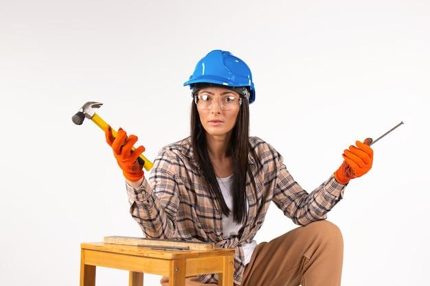 Femme brune constructeur avec des outils se penche sérieusement sur la caméra sur fond blanc isolé