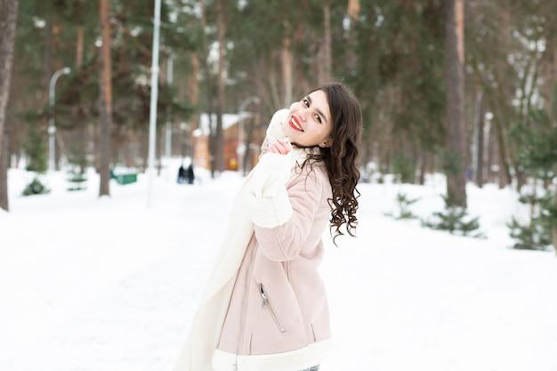 Femme brune cool marchant dans la forêt en hiver. espace pour le texte
