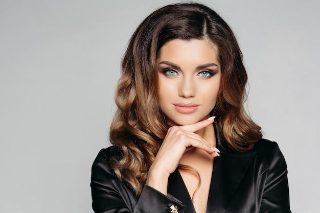Femme brune en costume noir regardant sérieusement et se touchant le visage avec les doigts.