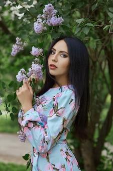 Femme brune dans les branches d'un bel arbre en fleurs. robe d'été courte sur le corps de la fille. promenade printanière dans le parc, ambiance romantique. portrait d'une fille près des buissons et des arbres