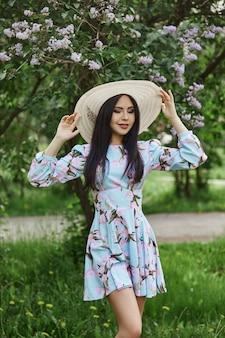 Femme brune dans les branches d'un bel arbre en fleurs.