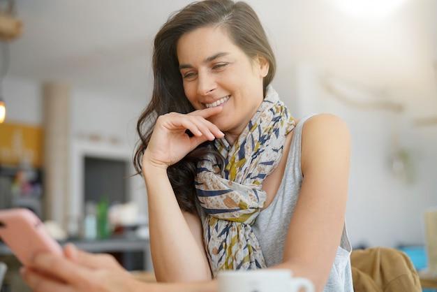 Femme brune dans un café à l'aide de smartphone