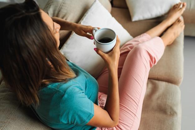 Femme brune dans une maison confortable, tenant une tasse de thé, regardant la fenêtre et se détendre sur un canapé moderne