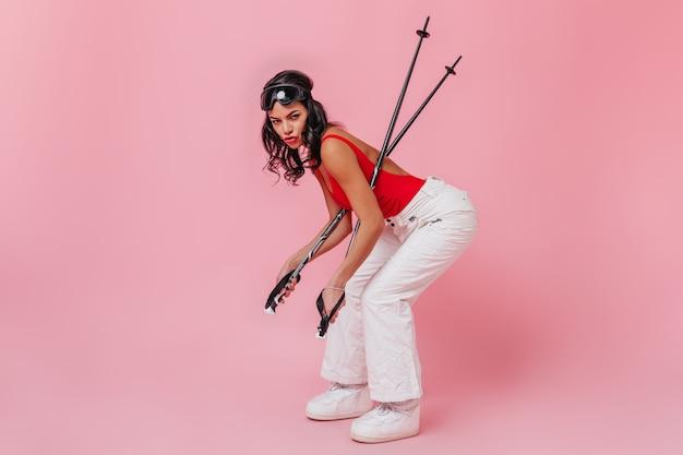 Femme brune drôle tenant des bâtons de ski