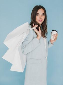 Femme brune avec du café et des sacs à provisions sur l'épaule