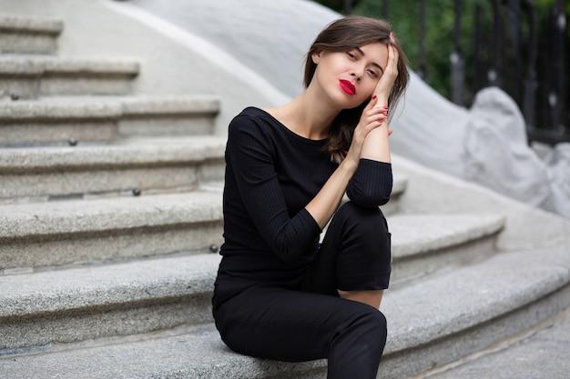 Une femme brune élégante aux lèvres rouges porte un costume noir assis sur les escaliers en béton blanc