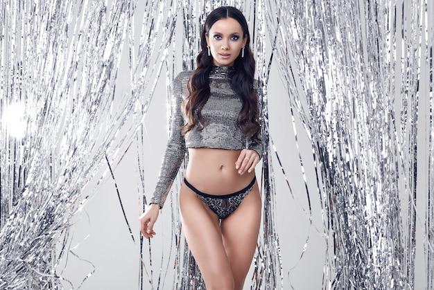Femme brune élégante avec un corps parfait dans un haut à sequins luxueux