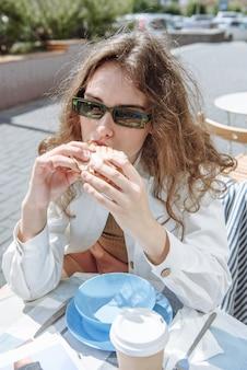 Femme brune élégante avec des lunettes burger mordant en portrait de restaurant
