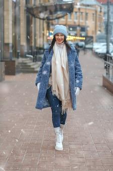 Femme brune élégante en manteau marchant dans la ville par temps de neige