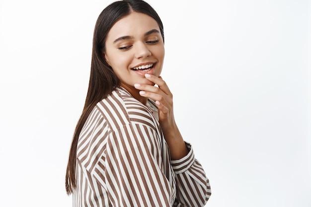 Femme brune élégante touchant ses lèvres et souriante, regardant vers le bas avec un visage coquet et séduisant, debout contre un mur blanc