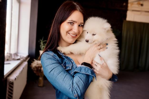 Femme brune embrasse avec animal de compagnie - chiot blanc moelleux à la maison