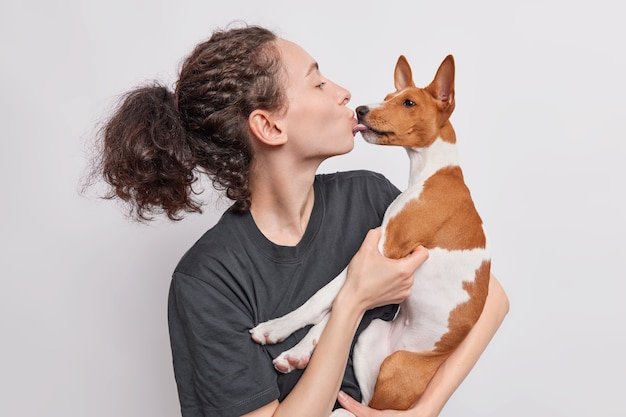 Une femme brune embrasse un chien basenji amoureux de son animal de compagnie préféré exprime des soins vêtus d'un t-shirt noir isolé sur blanc