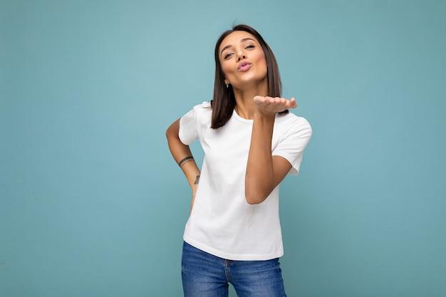 Femme brune avec des émotions sincères portant un tshirt blanc décontracté pour maquette isolé sur bleu