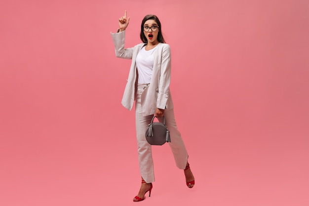 Femme brune a une excellente idée et pose sur fond rose. belle femme d'affaires dans des vêtements élégants et avec des mouvements de sac à main gris.