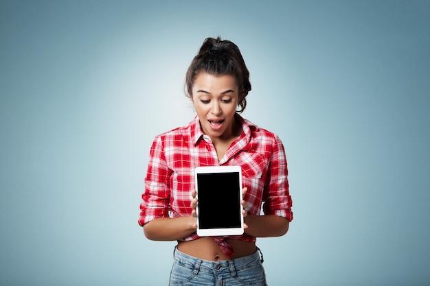 Femme brune expressive portant une chemise rayée et tenant la tablette