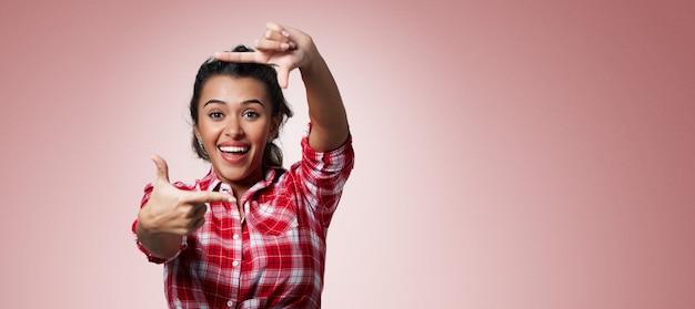 Femme brune expressive portant une chemise rayée