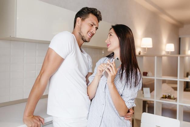 Femme brune extatique aux cheveux longs à la recherche dans les yeux du mari avec sourire