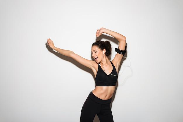 Femme brune fitness bouclée joyeuse, écouter de la musique par smartphone