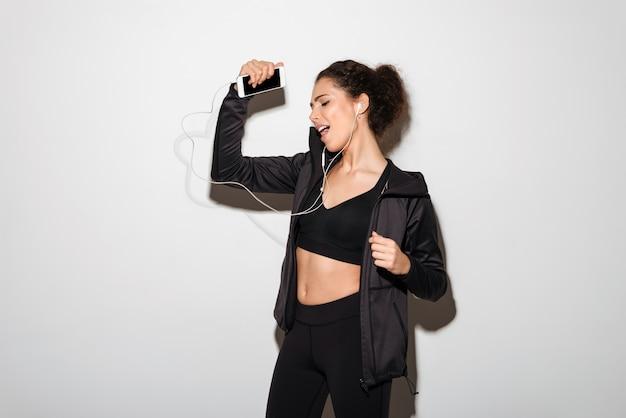 Femme brune fitness bouclée ludique, écouter de la musique avec les yeux fermés