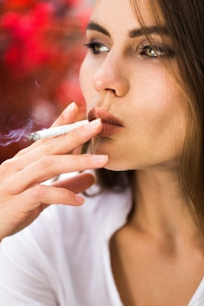 La femme brune fume un cigare