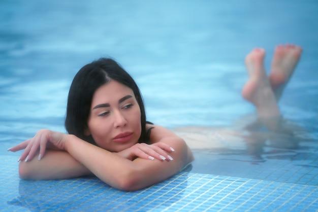 Une femme brune glamour se trouve dans l'eau thermale de la piscine du spa et se détend. mise au point sélective douce sur les yeux du modèle.