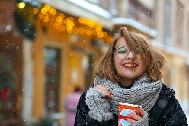 Une femme brune heureuse porte une écharpe tricotée et un manteau boit du café dans la rue pendant les chutes de neige. espace libre
