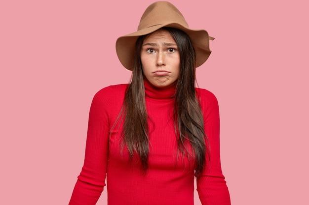 Une femme brune incertaine a une expression désemparée, regarde avec incrédulité, serre les lèvres