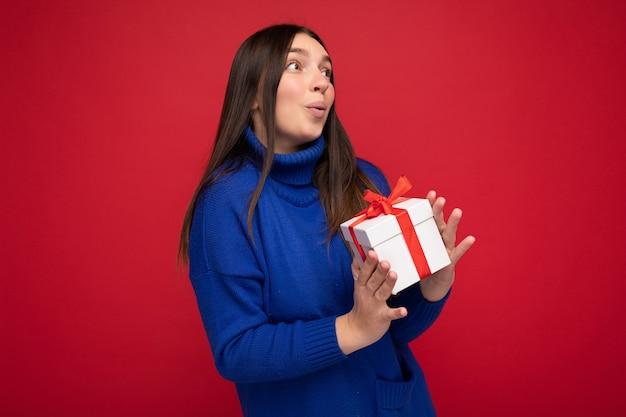Femme brune isolée sur un mur rouge portant un pull décontracté bleu tenant une boîte-cadeau blanche et regardant sur le côté.