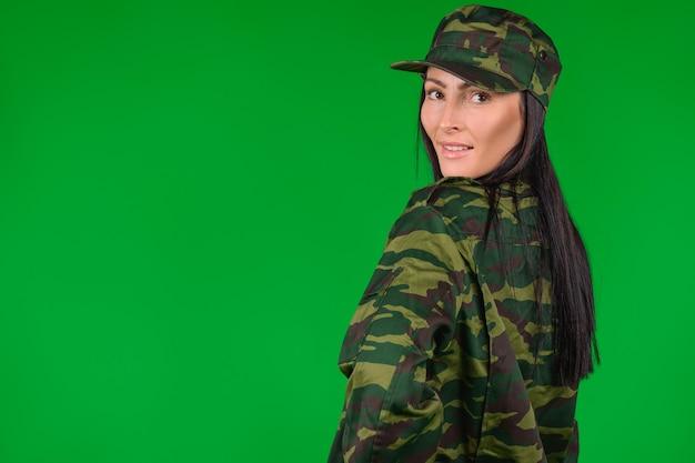 Femme brune avec un joli sourire et dans un uniforme militaire posant sur un fond vert avec un espace latéral vide.